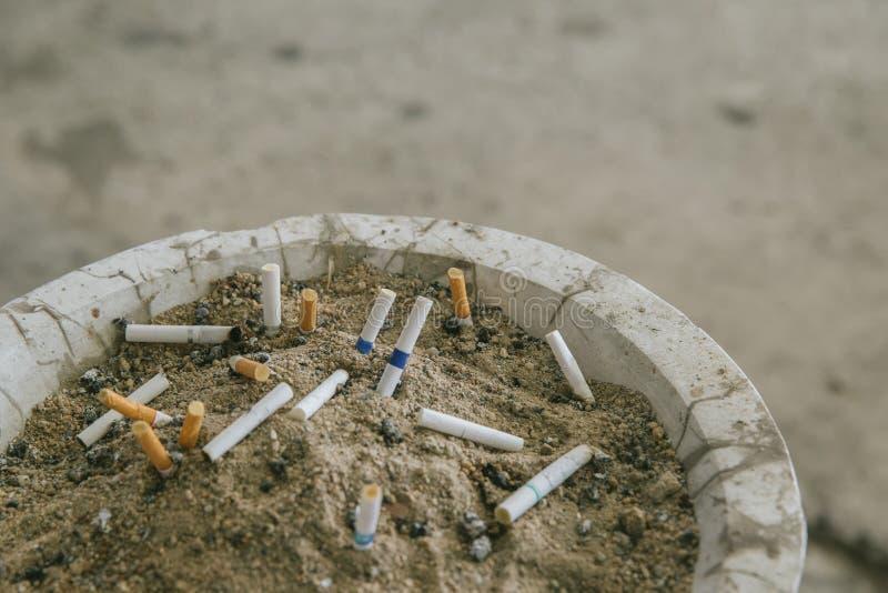 许多在沙子烟灰缸的香烟残余部分 其余在烟灰缸的香烟 有香烟残余部分的许多类型在沙子的  库存图片