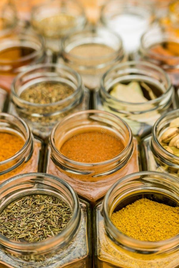 许多在玻璃瓶子的五颜六色的鲜美调味料香料 库存照片