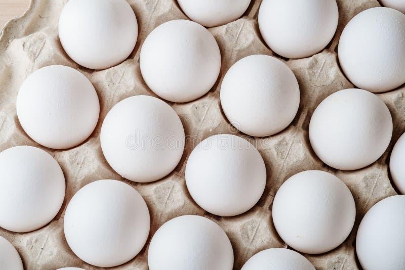 许多在盘子箱子的白色鸡蛋食物 免版税库存图片