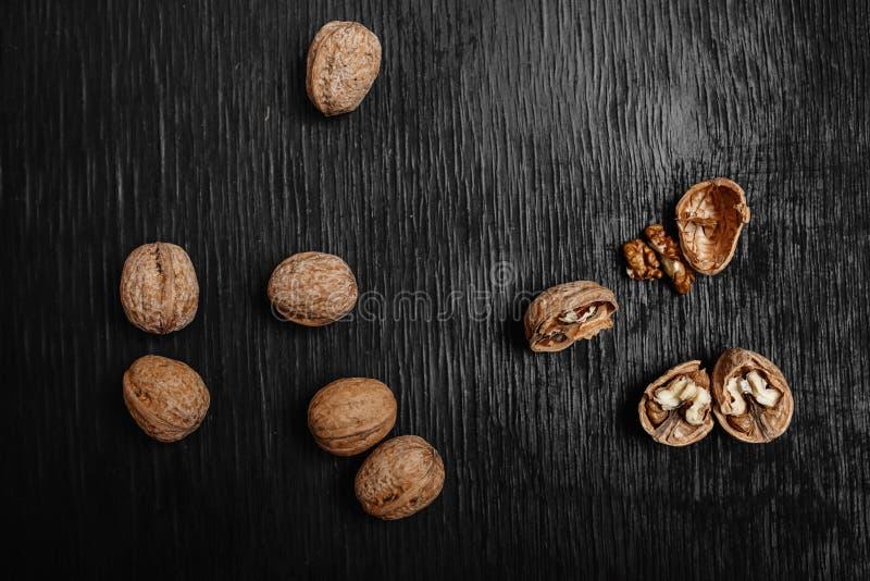 许多在黑木背景的新鲜的坚果 设计师的最优方法 免版税库存照片
