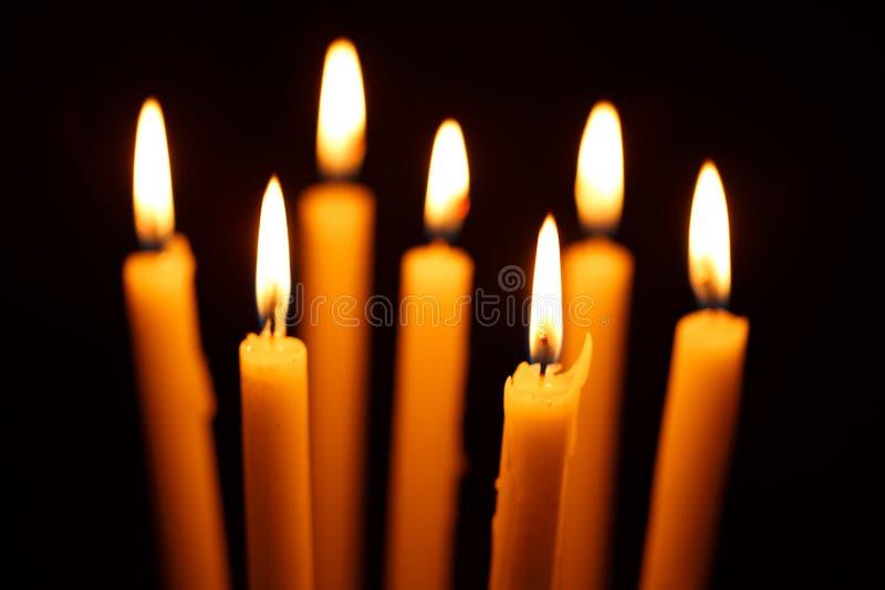 许多在黑色的燃烧的蜡烛 图库摄影