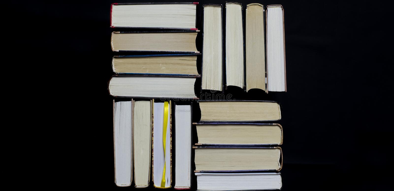 许多多彩多姿的厚实的开放在黑暗的背景书摊 在书是老圆的玻璃和一个开放笔记本有a的 图库摄影
