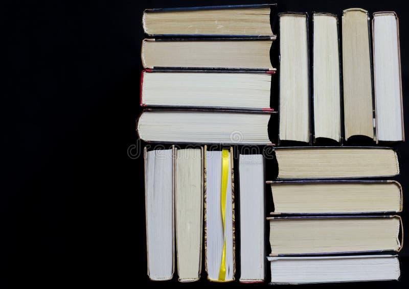 许多多彩多姿的厚实的开放在黑暗的背景书摊 在书是老圆的玻璃和一个开放笔记本有a的 免版税库存照片