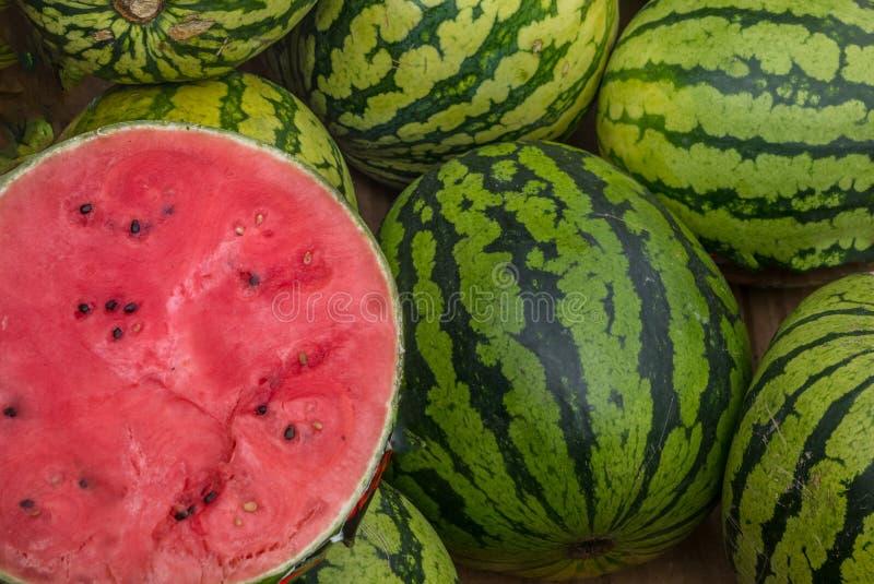许多大甜绿色西瓜和一个被切的西瓜 年轻绿色西瓜 库存照片