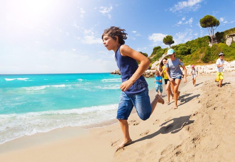 许多孩子在沙滩和有乐趣跑 免版税库存图片