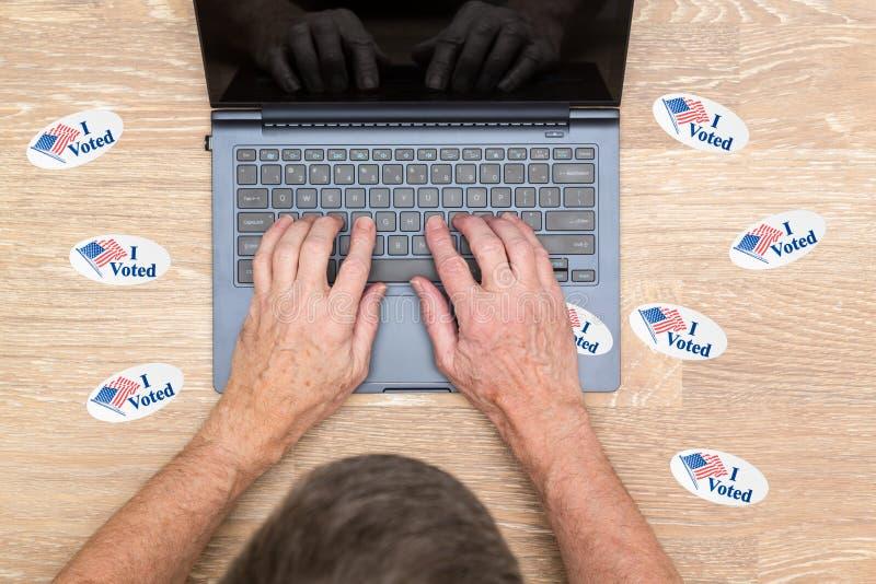 许多我投票了在黑客书桌上的贴纸  库存照片