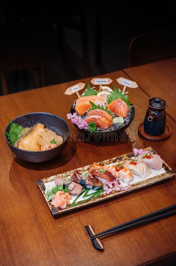 许多日本寿司、Donburi和三文鱼sahimi在木头 库存照片