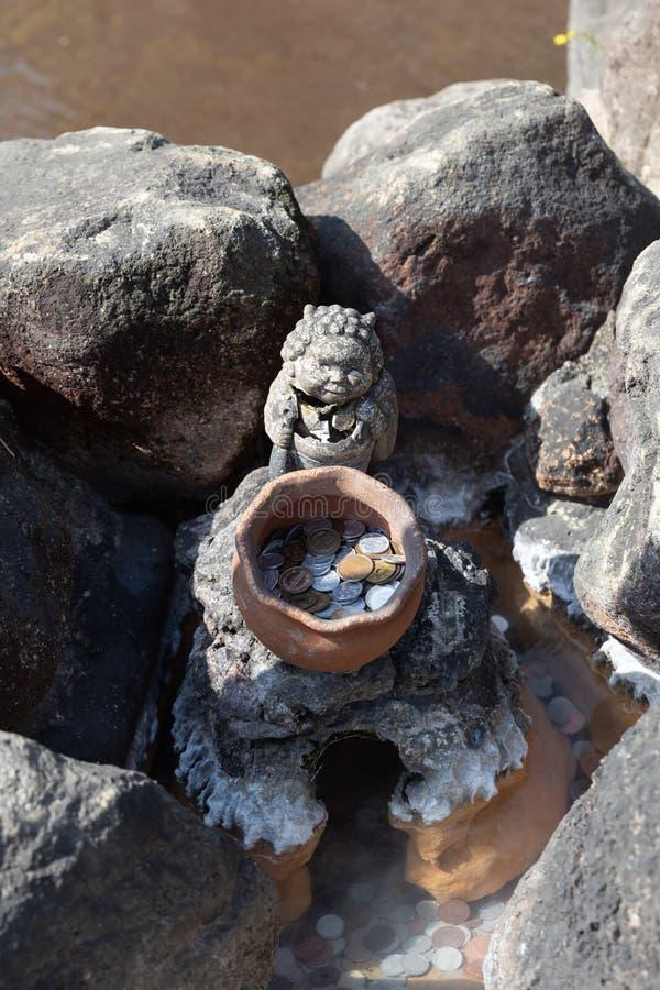 许多日本硬币在有黏土瓶子和雕象的池塘 免版税库存图片