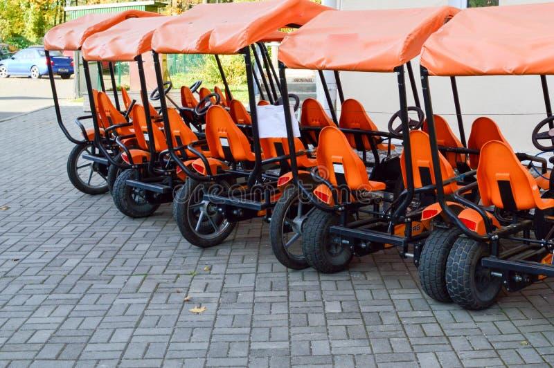 许多时兴的橙色单轮体育自行车、周期卡片家庭体育休闲的和旅游业与轮子和脚蹬 免版税库存照片