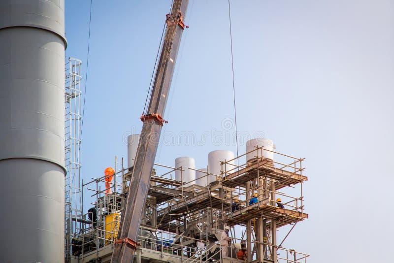 许多有起重机的塔工地工作和修造有天空蔚蓝背景,建筑工厂的脚手架 免版税库存图片