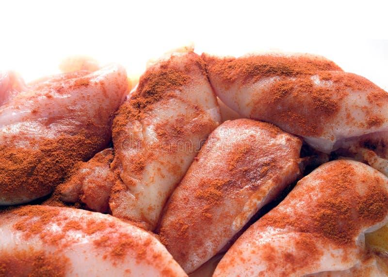 许多未加工的被切的鸡片断很好洒与被隔绝的红辣椒 免版税库存照片