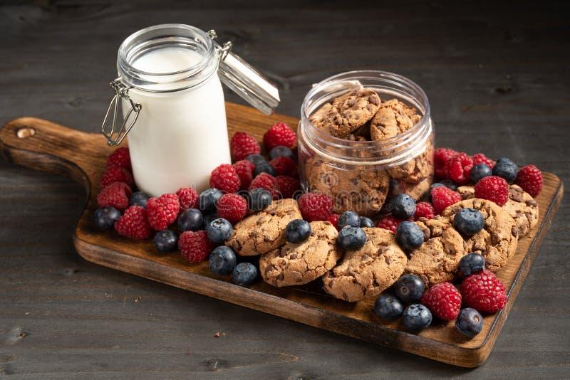 许多森林果子,一个瓶子牛奶和曲奇饼,被安置在木盛肉盘 库存照片