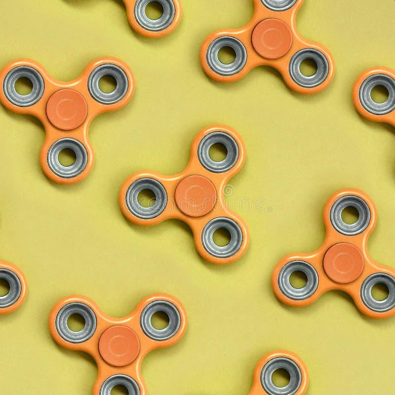 许多橙色坐立不安锭床工人在时尚淡色橘黄色纸纹理背景说谎  免版税图库摄影