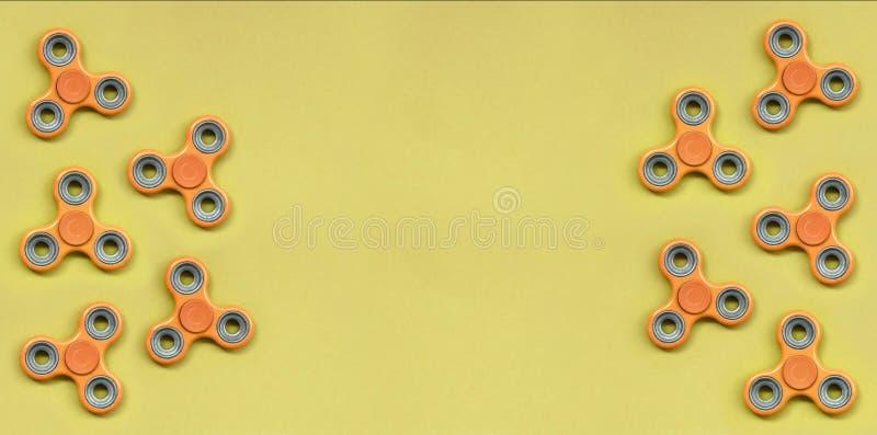 许多橙色坐立不安锭床工人在时尚淡色橘黄色纸纹理背景说谎  免版税库存图片