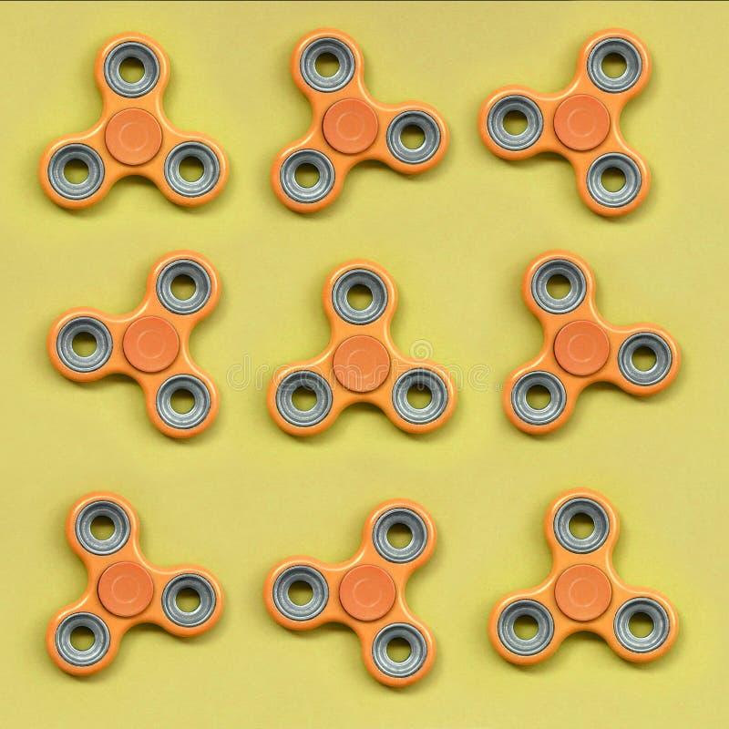 许多橙色坐立不安锭床工人在时尚淡色橘黄色纸纹理背景说谎  图库摄影