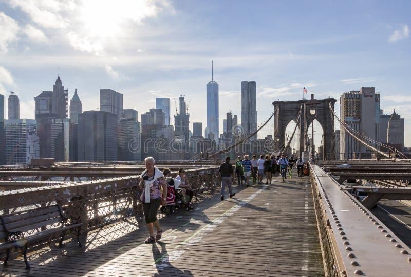 许多步行者和骑自行车者布鲁克林大桥的上甲板的有曼哈顿的在背景中,纽约,美国 免版税库存图片