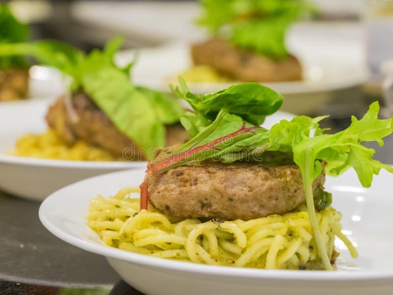 许多汉堡牛排服务用面条和菜 免版税库存照片