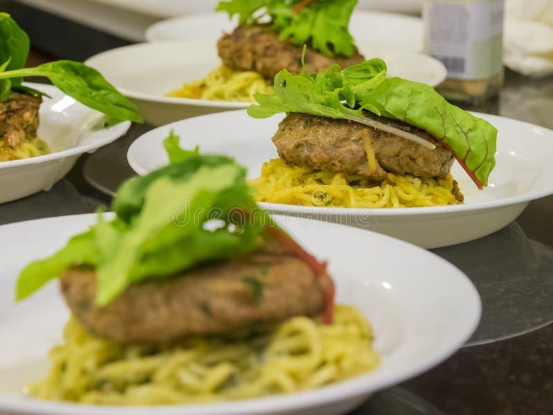 许多汉堡牛排服务用面条和菜 免版税图库摄影