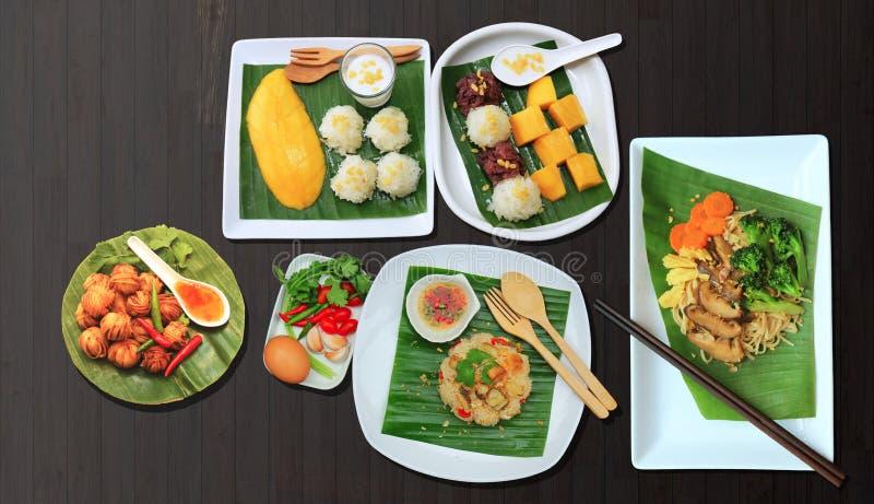 许多泰国食物例如芒果糯米 油煎的油煎的罗非鱼和被油炸的被包裹的猪肉用面条 免版税库存图片