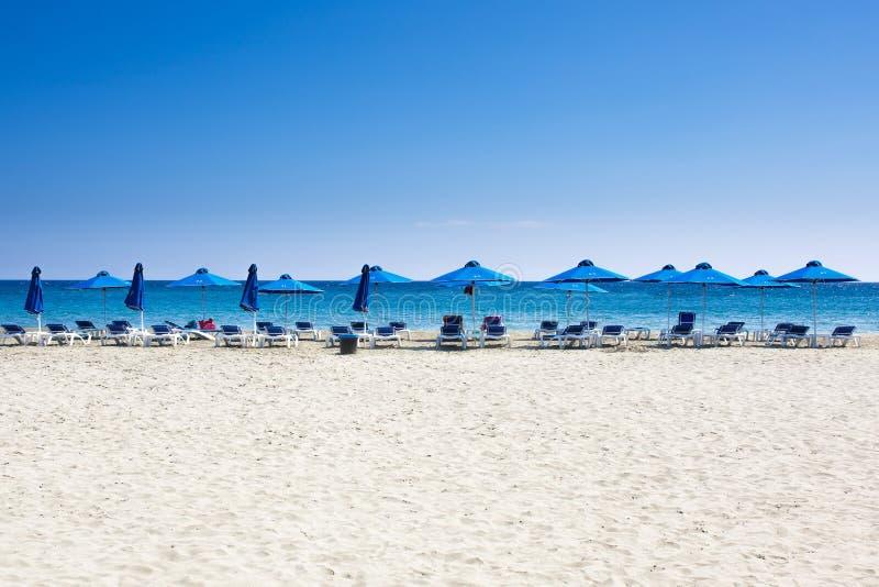 许多海滩睡椅和伞在白色沙子海靠岸与蓝天 免版税图库摄影