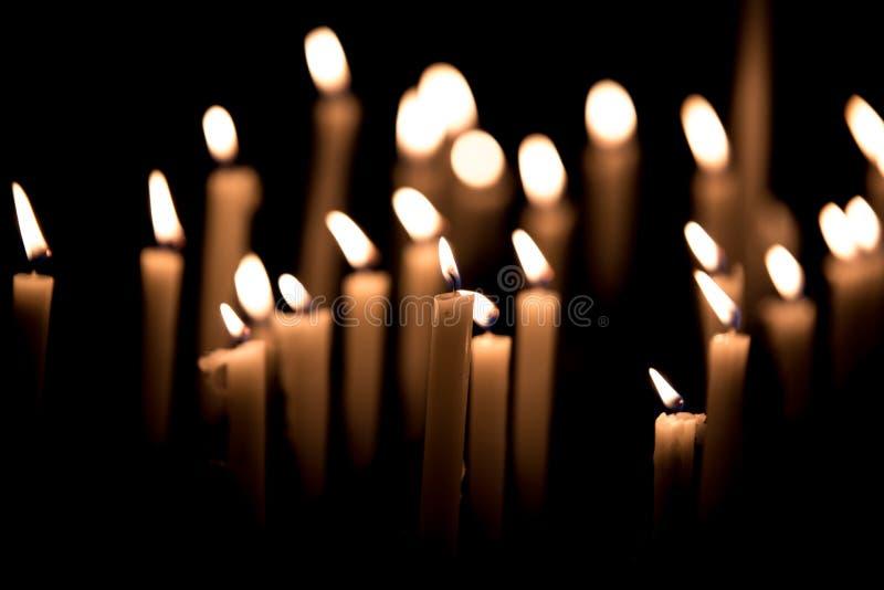 许多灼烧的蜡烛- candels光在黑背景的教会里 免版税图库摄影