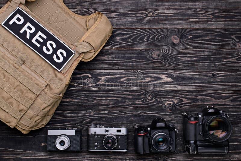 许多照相机和身体装甲在木桌上 免版税图库摄影