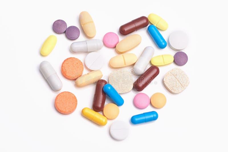 许多片剂和胶囊在心脏形状说谎在白色背景 不同的五颜六色的医学药物 医学和治疗conce 库存照片