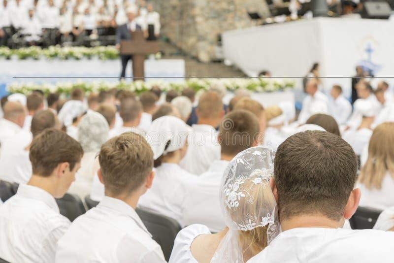 许多男人和妇女祈祷给耶稣 年轻人基督徒唱诗班和女孩在公园唱基督徒歌曲并且赞美上帝 模糊的 免版税图库摄影