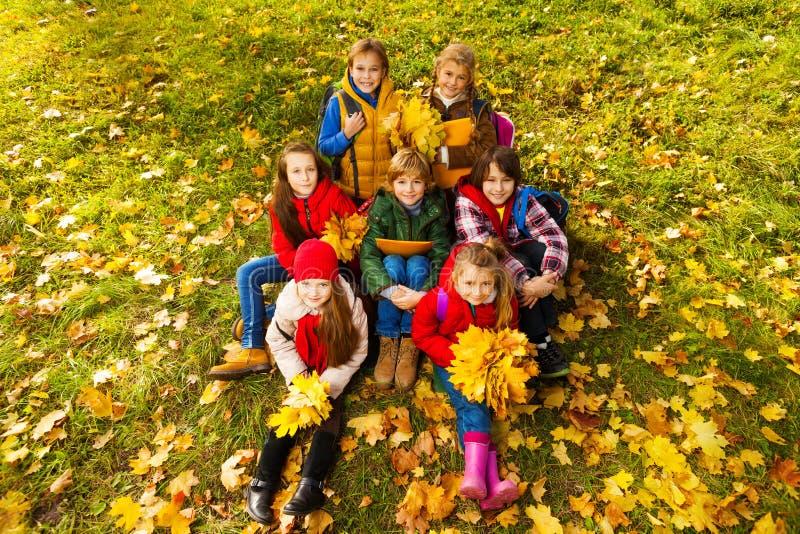 许多男孩和女孩秋天草坪的 免版税库存照片