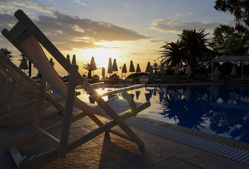 许多白色躺椅在游泳场附近站立反对黎明天空和沙滩伞的背景 图库摄影