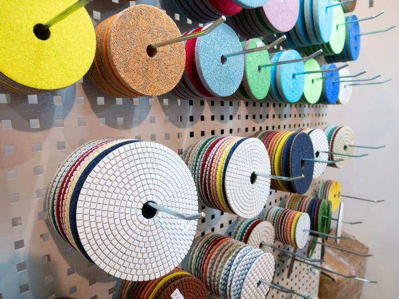 许多的特写镜头垂悬在立场的工业电动工具的不同的擦亮的和研的可替换的盘在硬件设备 免版税库存图片