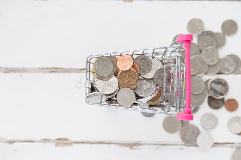 许多的顶视图在微型手推车的硬币有从推车的一些硬币下落的 免版税库存图片