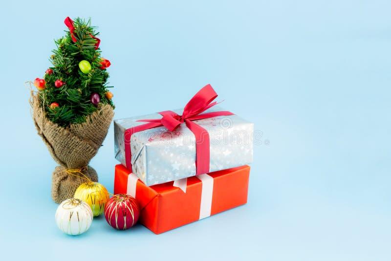 许多礼物盒白色在蓝色backgr隔绝的丝带球和树 图库摄影