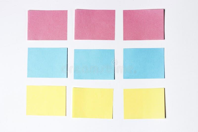 许多空的多彩多姿的办公室贴纸大模型在木背景的 复制空间,文本的空间 概念笔记本办公室笔手表 免版税库存图片