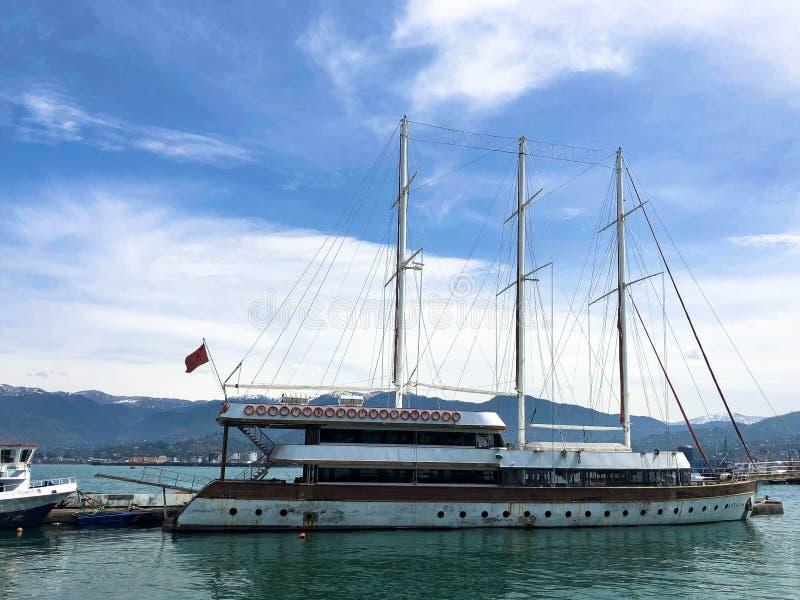 许多船、小船、巡航划线员在口岸和水在热带海避暑胜地反对天空蔚蓝和高山 免版税库存照片