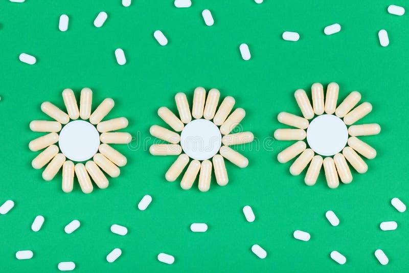 许多药片和胶囊与抽象形式在绿色 免版税库存图片