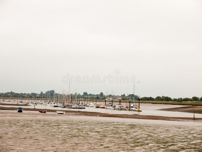 许多被停泊的小船在河安静阴云密布白色天停放了 库存图片