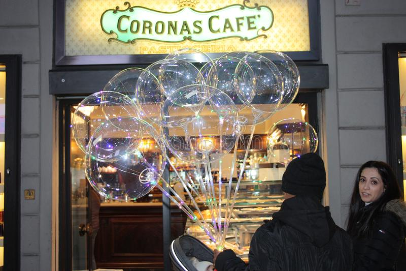 许多透明气球的卖主在一家明亮的党商店前面的 图库摄影