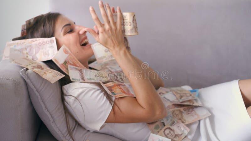 许多钞票在慢动作的空气天花板飞行 女孩说谎和在她的很多金钱秋天 愉快的妇女高兴 免版税库存照片