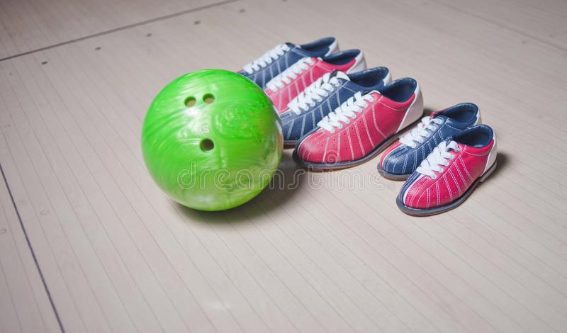 许多鞋子和球在地板上在滚保龄球的俱乐部 免版税库存照片