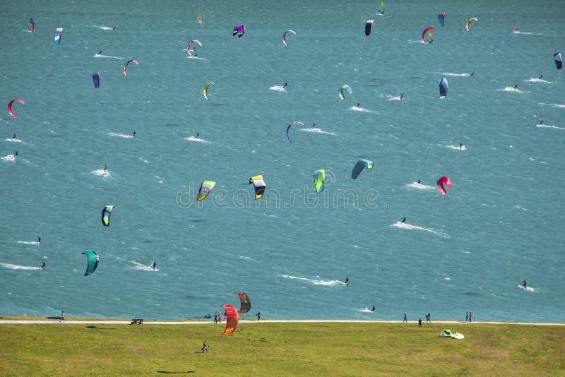 许多Kitesurfers和风帆冲浪者在湖 库存照片