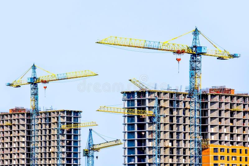 建设中两个多层的大厦 许多起重机 现代住房的建筑 免版税库存图片