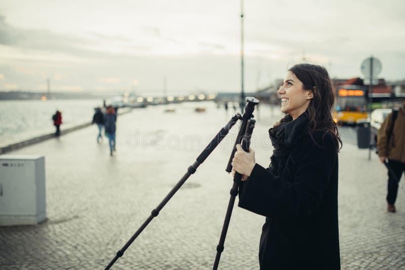 设定日落/日出日志曝光的年轻热心女性摄影师轻量级碳旅行三脚架仍然射击了 免版税库存图片