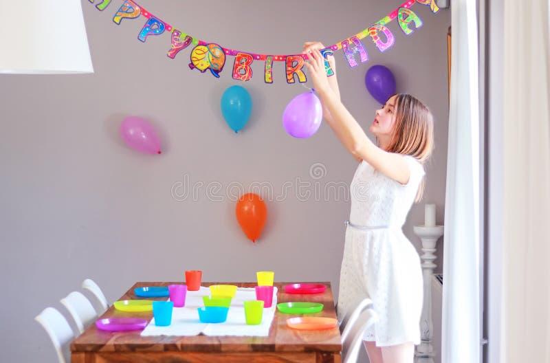 设定桌和垂悬气球的愉快的青春期前的女孩装饰准备对孩子生日宴会的房子 免版税库存图片