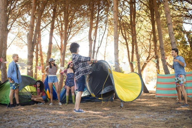 设定他们的帐篷的年轻朋友在乡下 库存图片