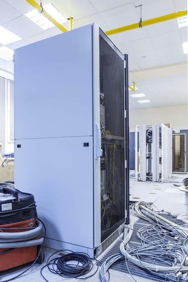 设施和缚住的过程在一个现代数据中心 有缆绳丝球的服务器机架在被拆卸的服务器旁边的 免版税库存照片