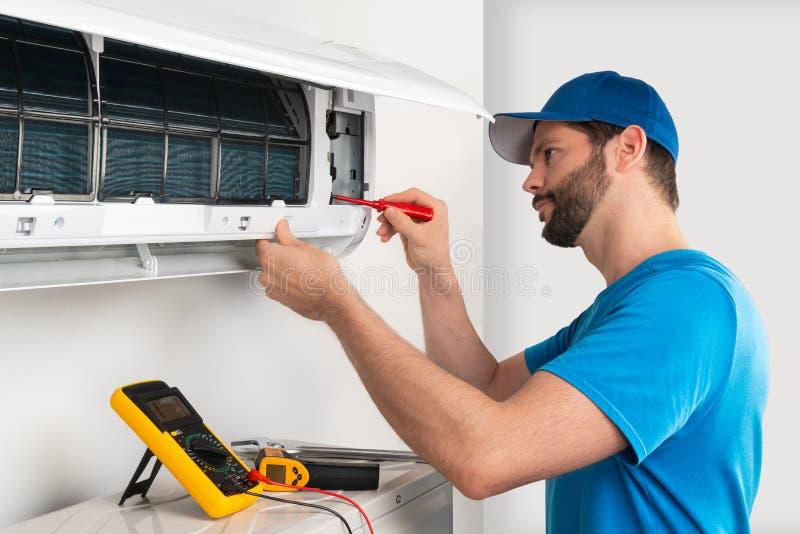 设施服务固定一个空调室内单位的修理维护由cryogenist technican工作者的有螺丝刀的 库存照片