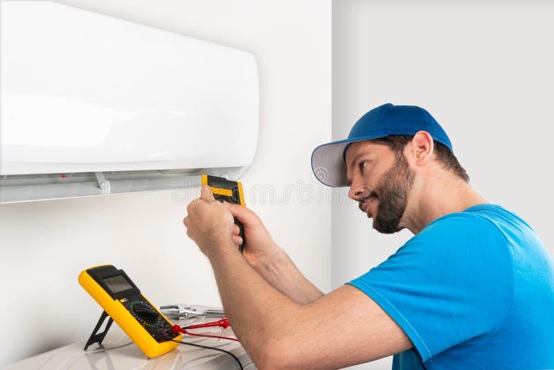 设施服务固定一个空调室内单位的修理维护,通过cryogenist technican工作者检查 免版税库存照片