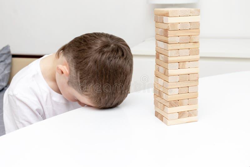 设法一个乏味青春期前的白种人的男孩打木块塔棋招待自己 库存照片