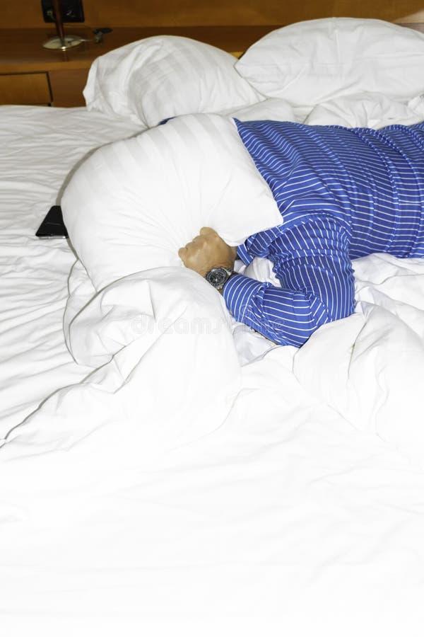设法一个的人睡觉在家避免附近噪声或旅馆的覆盖物耳朵 免版税库存照片